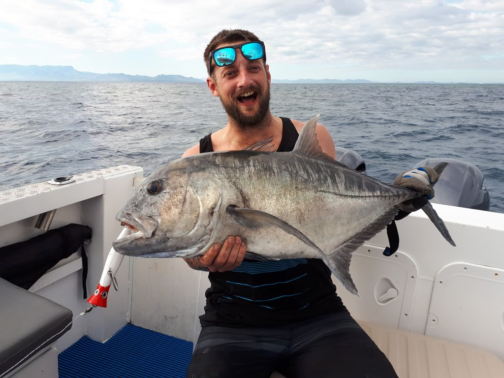 a smiling angler posing with a Giant Trevally caught on a lure