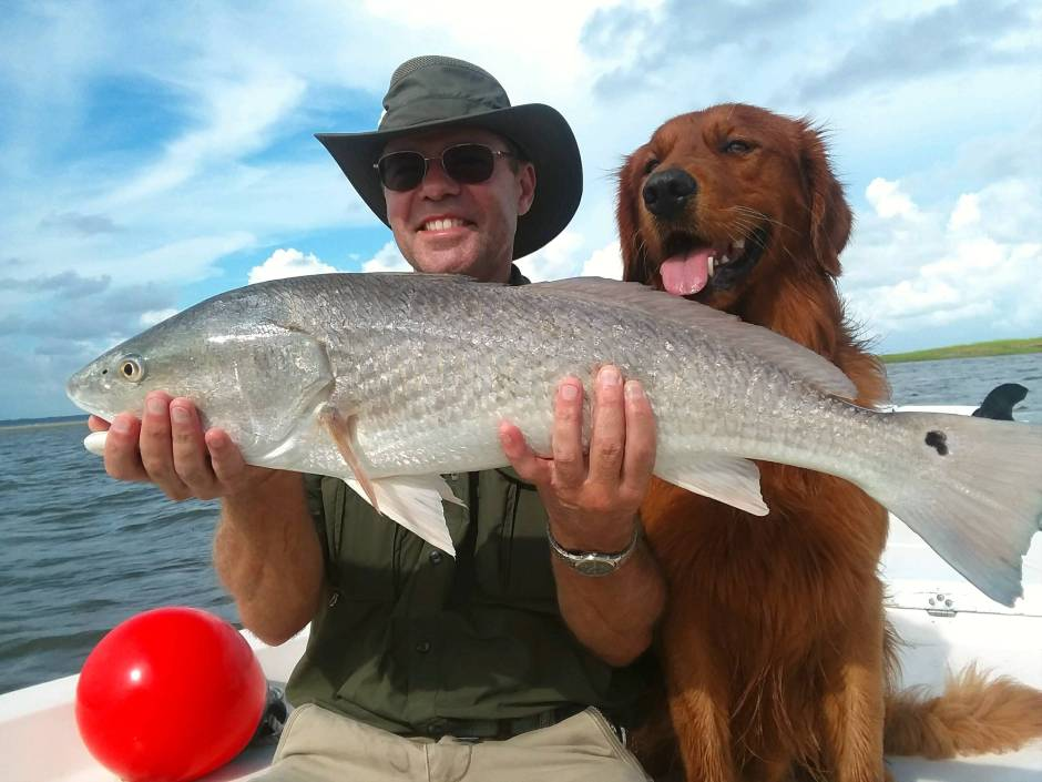 Paul Hale and dog Tripp with redfish