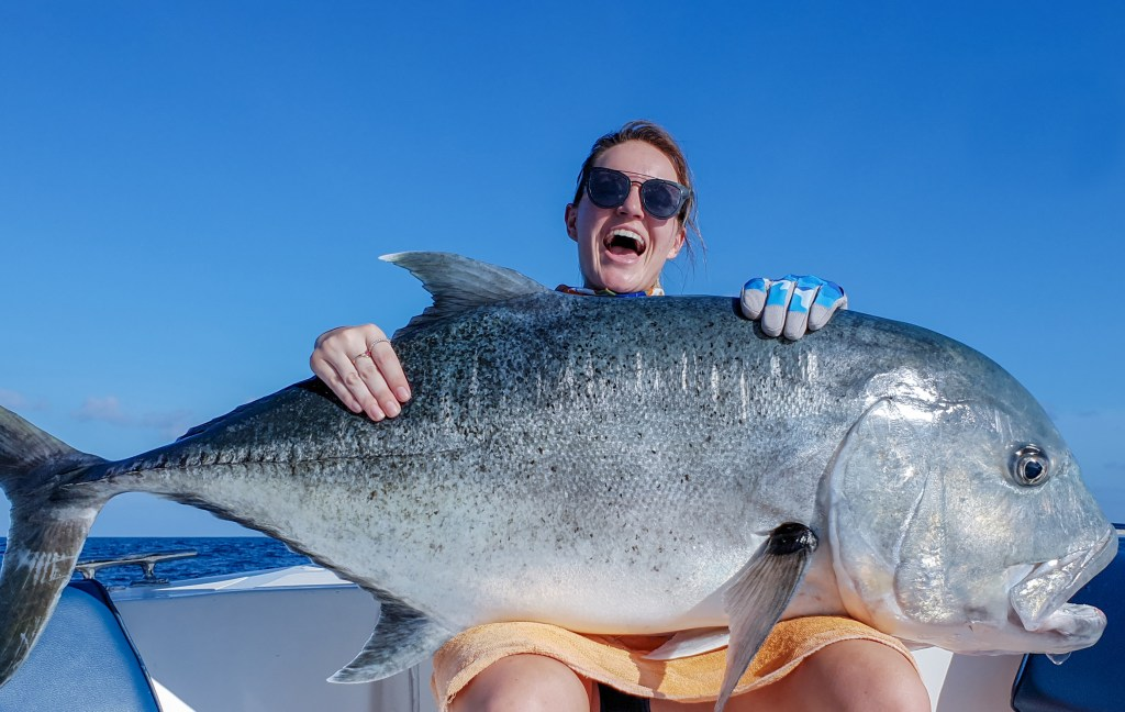 A female angler with a huge Giant Trevally on her lap