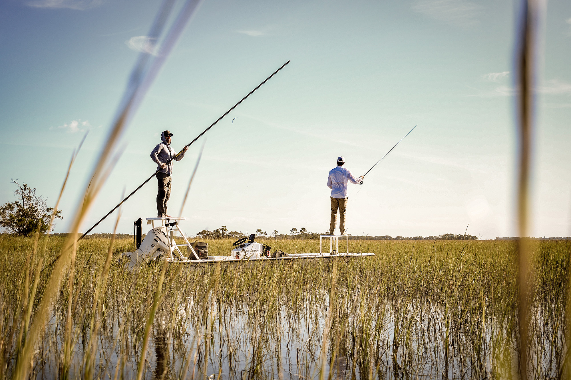 Two anglers fishing in shallow grass flats. One is poling the boat from behind while the other casts from a platform at the front