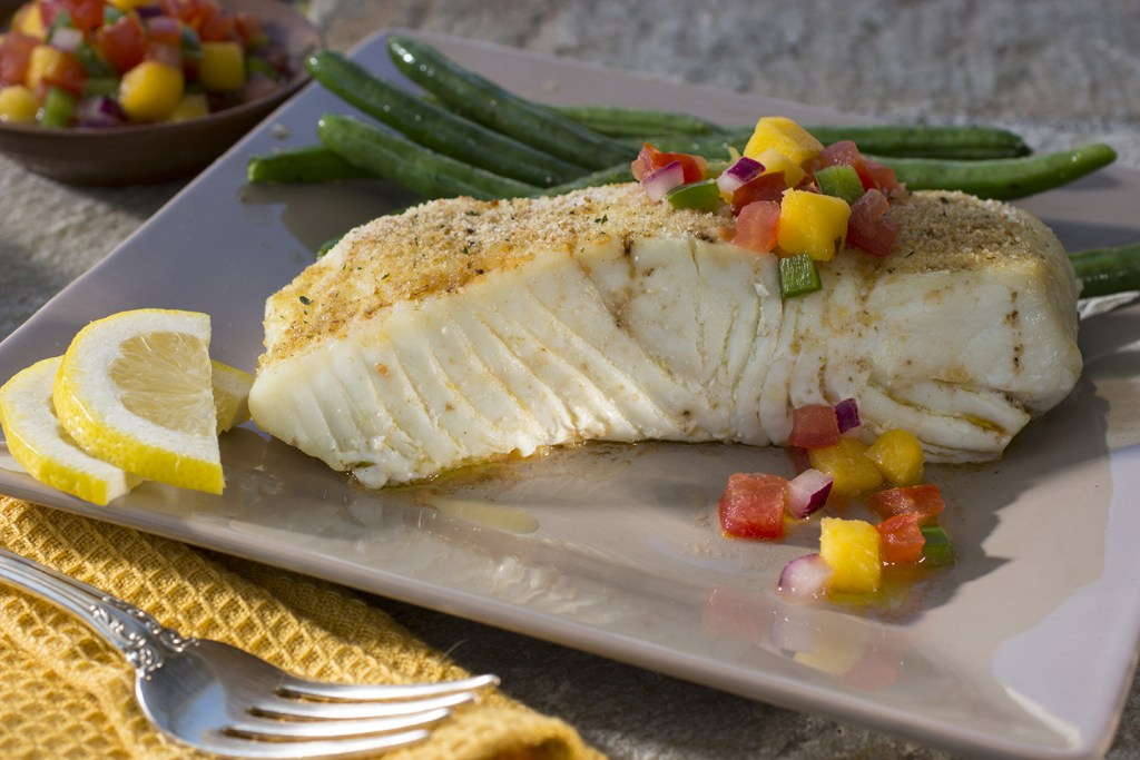 A piece of fried Halibut on a plate, with green beans behind it and chopped peppers and onions scattered on top. There are two slices of lemon on the left corner of the plate and a fork in the bottom left on a napkin.