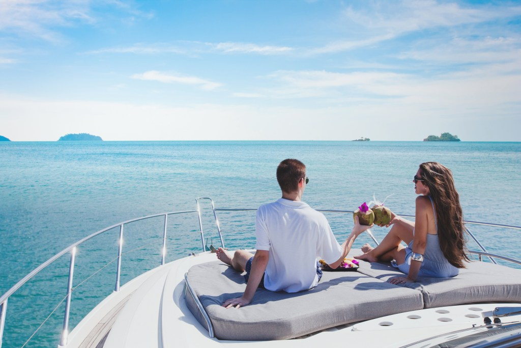 A happy couple toasting while sittnig at the front of a luxury charter boat at sea