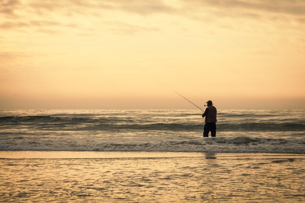 A man surf fishing on a beach on Hilton Head Island