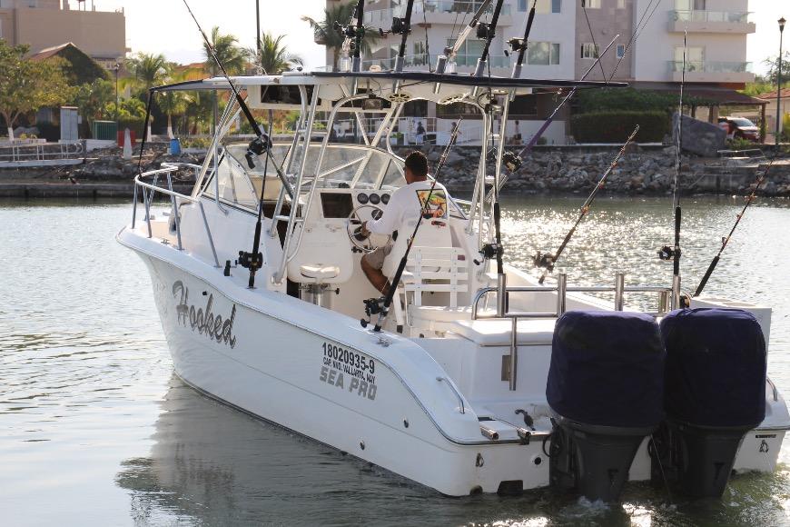 Man drives Hooked Sportfishing boat away from dock