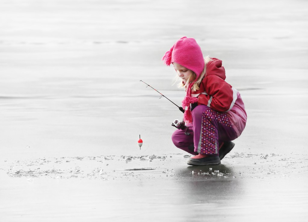 A little girl standing on a frozen lake with an ice fishing rod