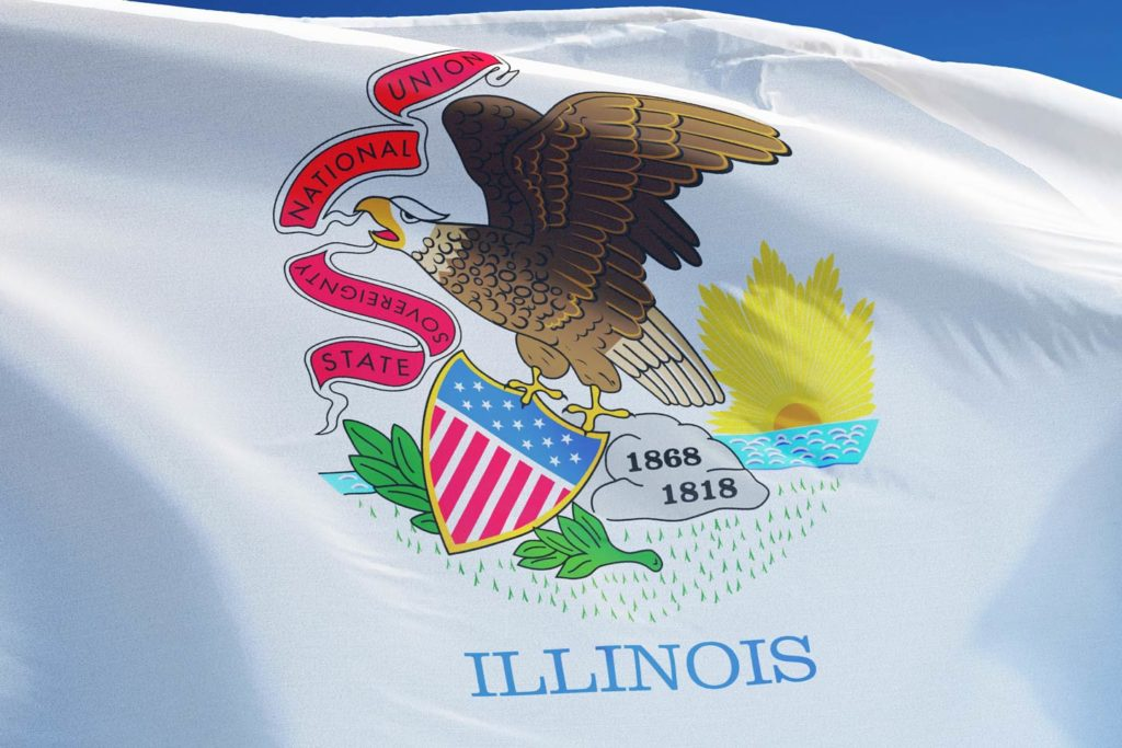 A closeup of the Illinois state flag showing the logo with a bit of blue sky visible