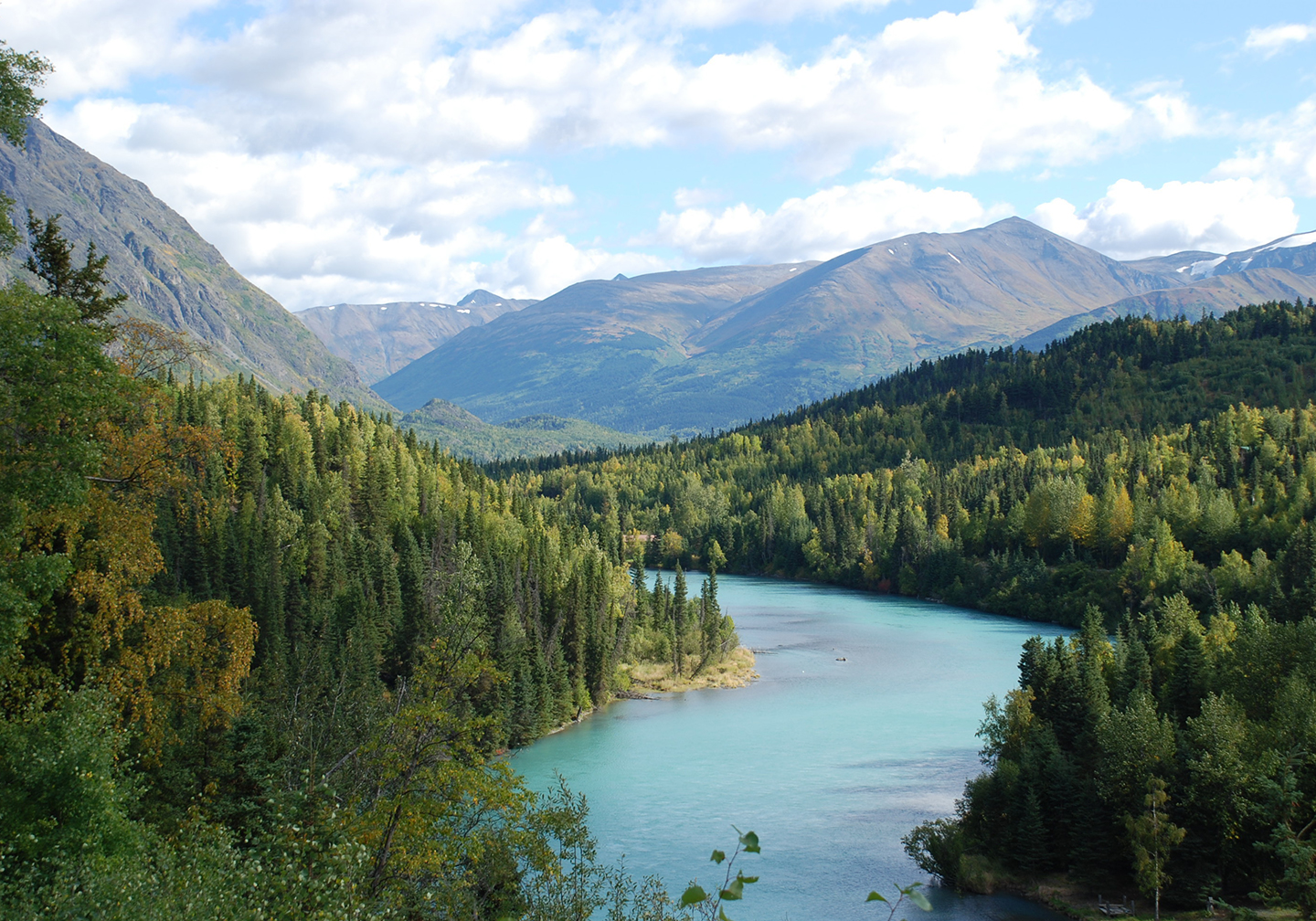 The Kenai River in Alaska, with dense forest on either side and mountains in the distance