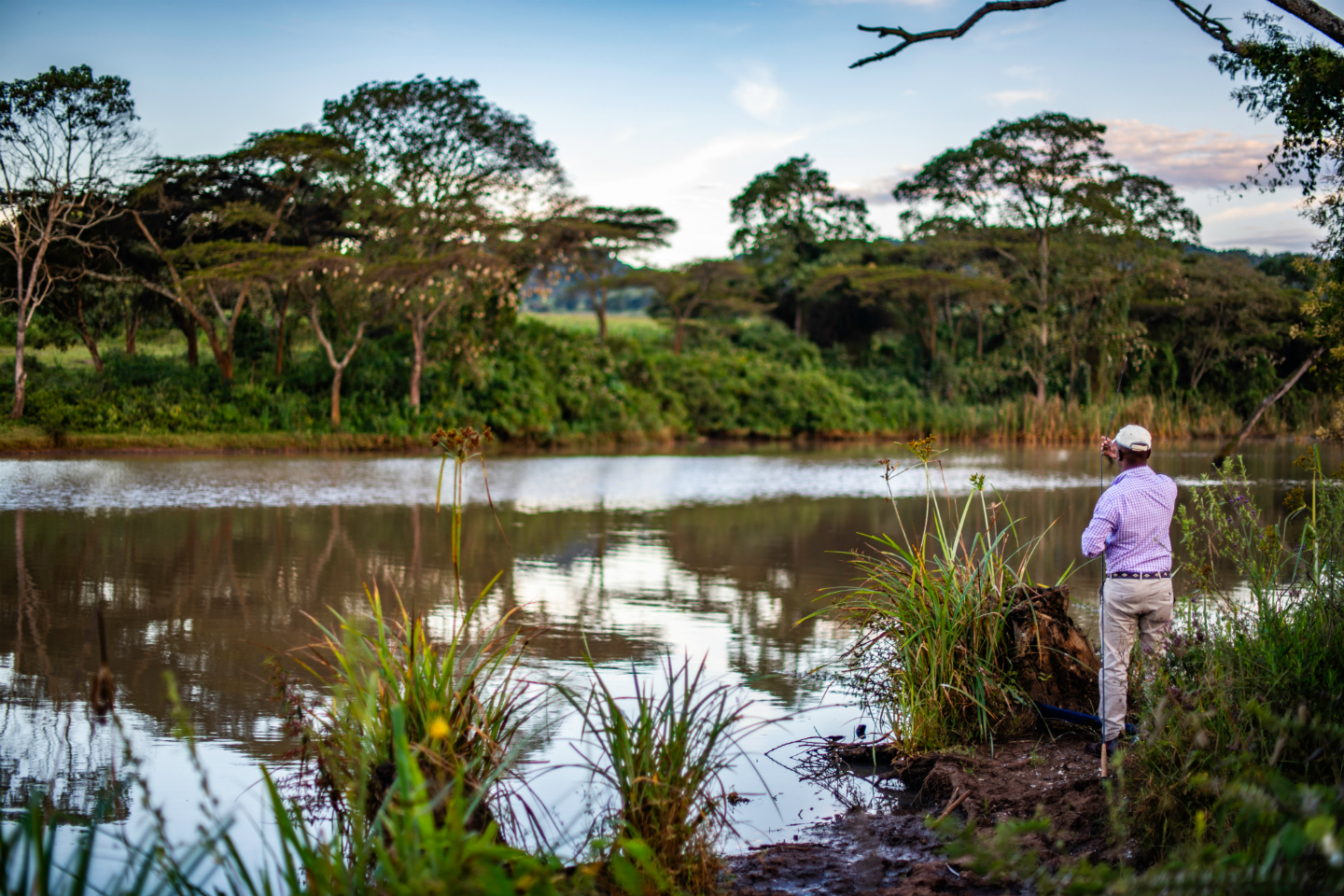 an angler holding a fly fishing rod on a river bank in Kenya