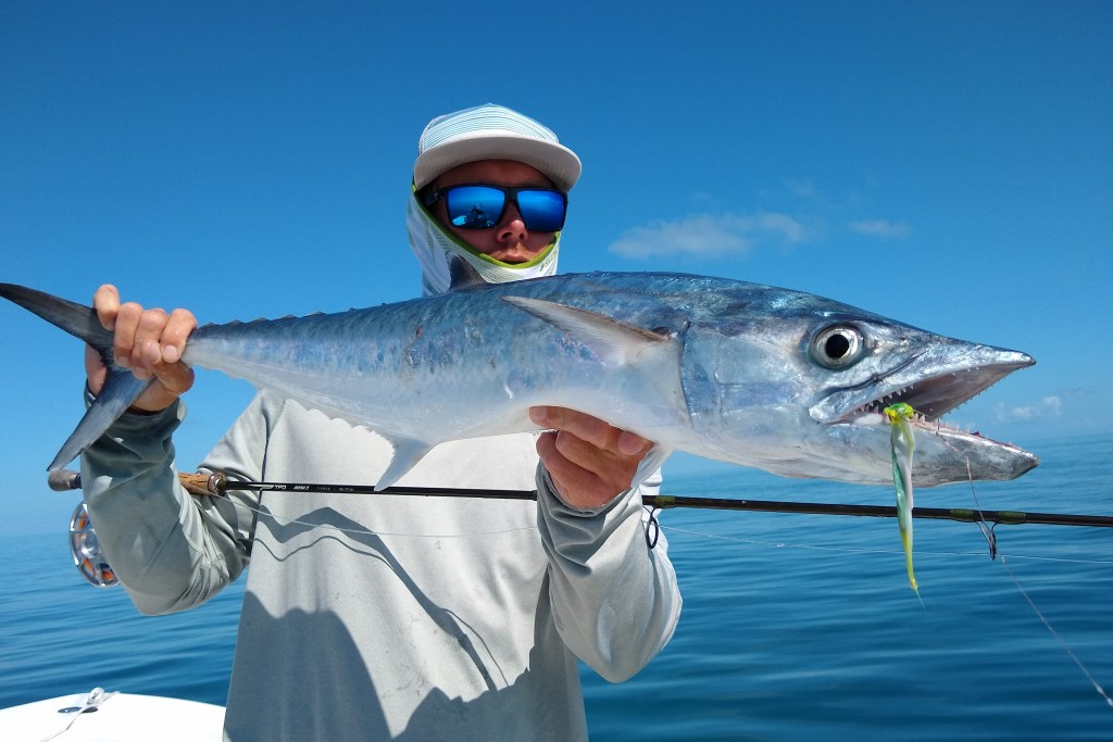 An angler holding a King Mackerel and a fly fishing rod on a charter fishing boat