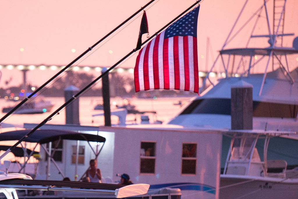 A US flag hanging off a charter fishing boat in a marina, with a pink evening sky in the distance