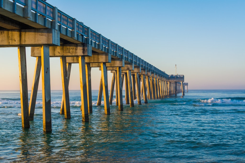 A wooden fishing pier stretching out into the ocean