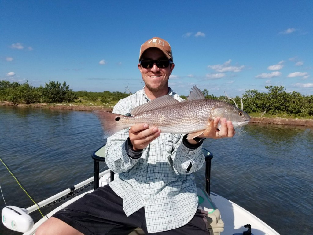 A man holds a Redfish on the river