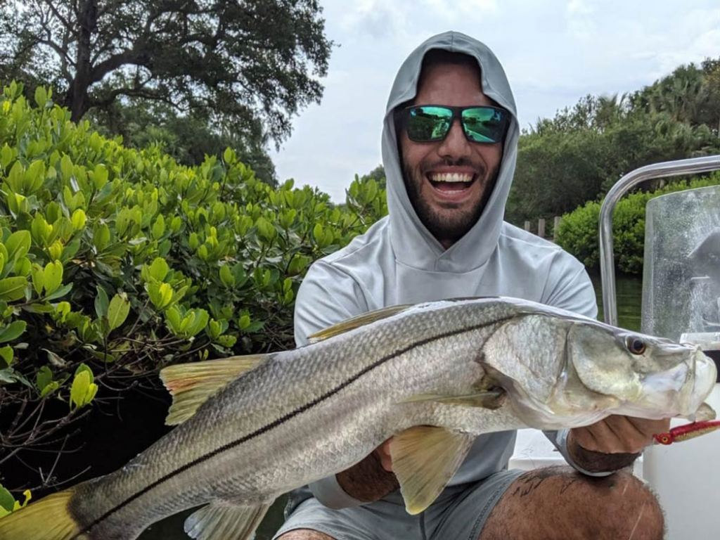 A smiling man holds a large Snook on the Indian River