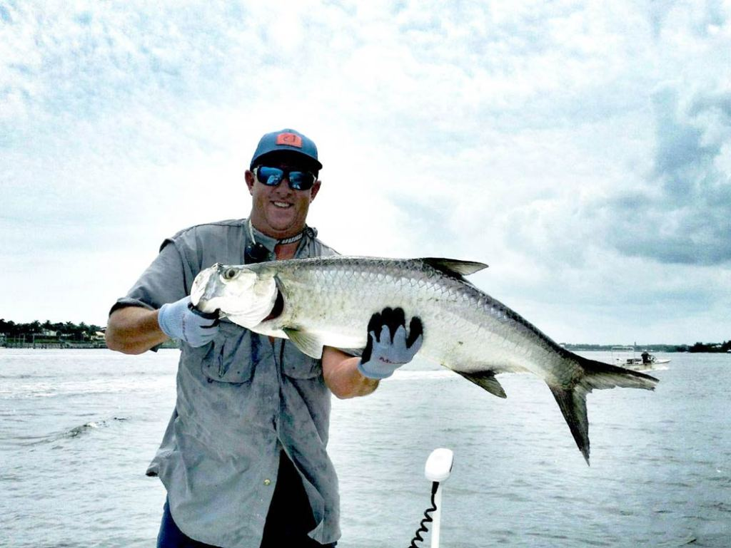A man stands on a boat on the Indian River holding a Tarpon