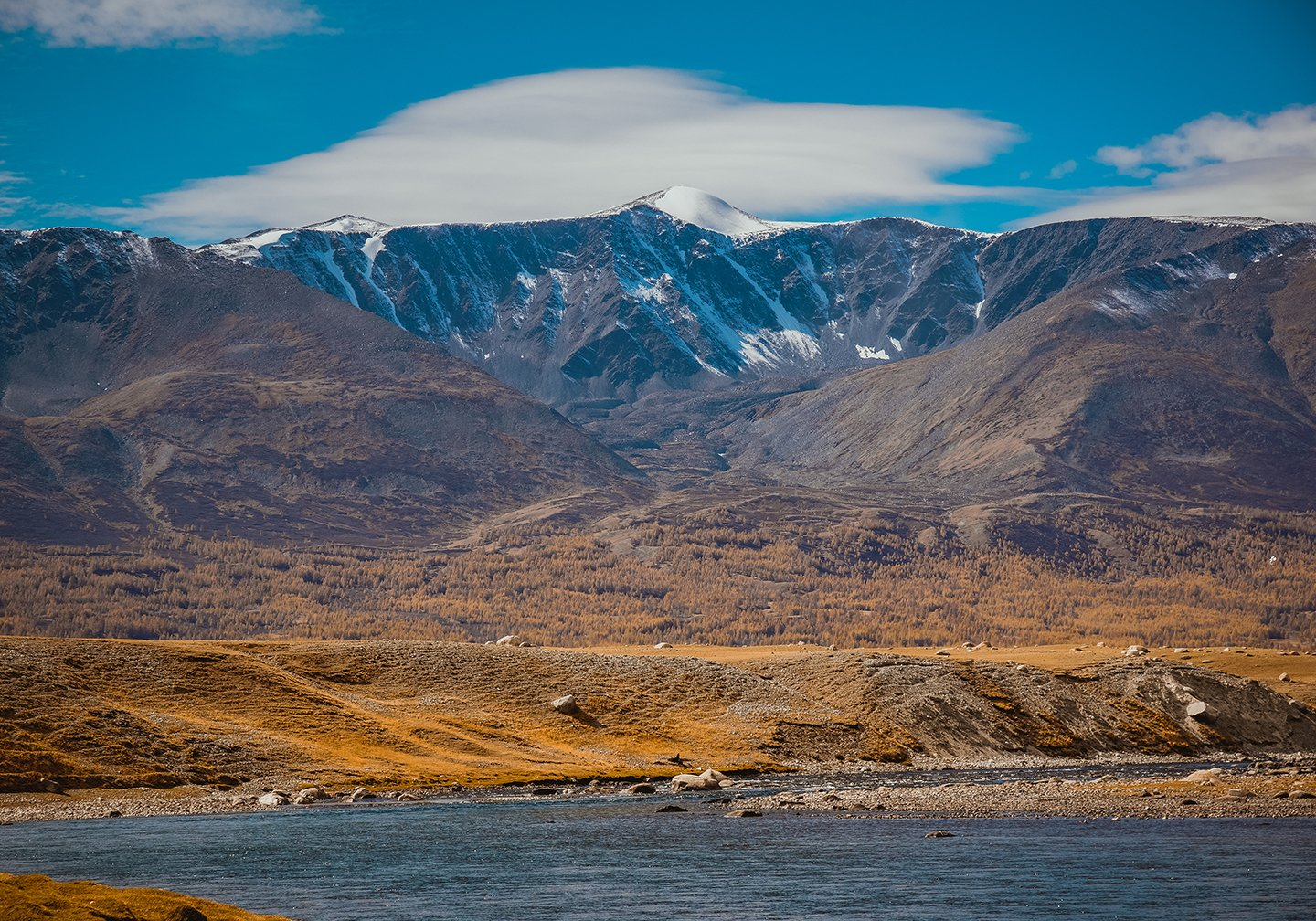 A view of the Mongolian Highlands with water in the foreground and snow-topped mountains in the distance