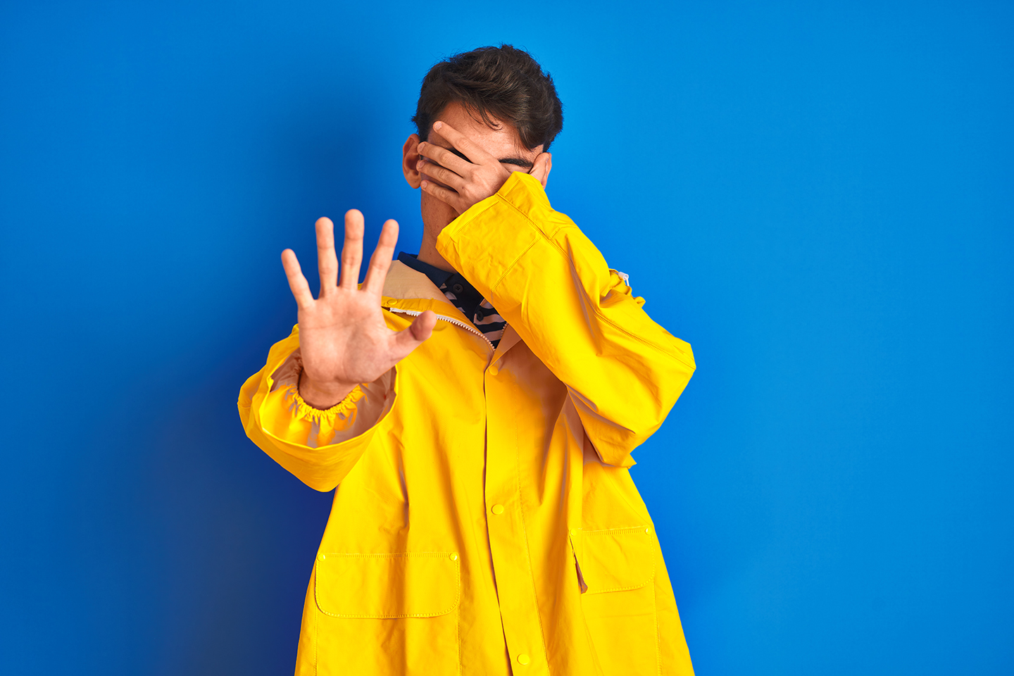 A young man in a yellow fisherman's jacket holding one hand to his face and the other out to the camera