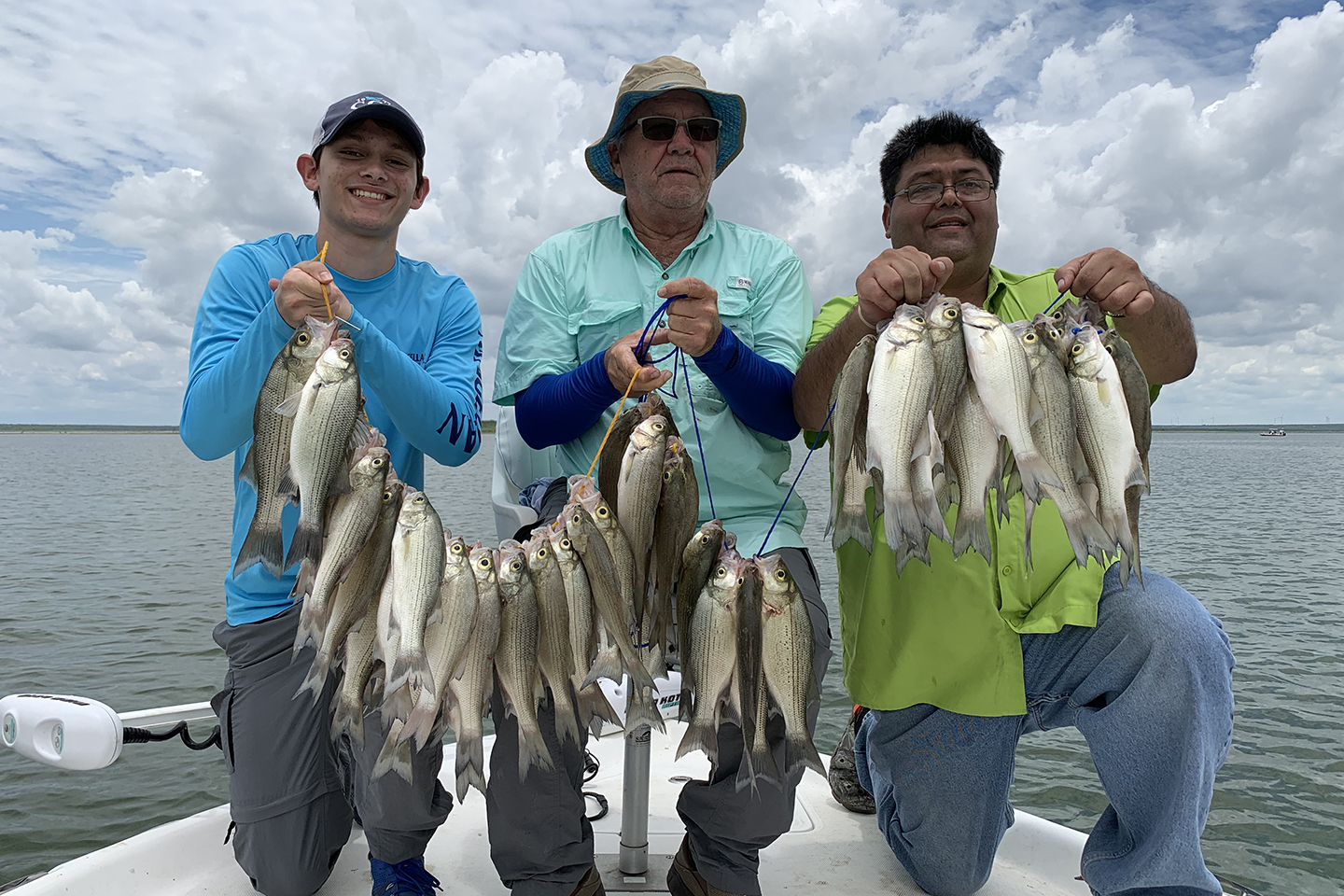 Three anglers holding stringers of White Bass on a boat in Oklahoma