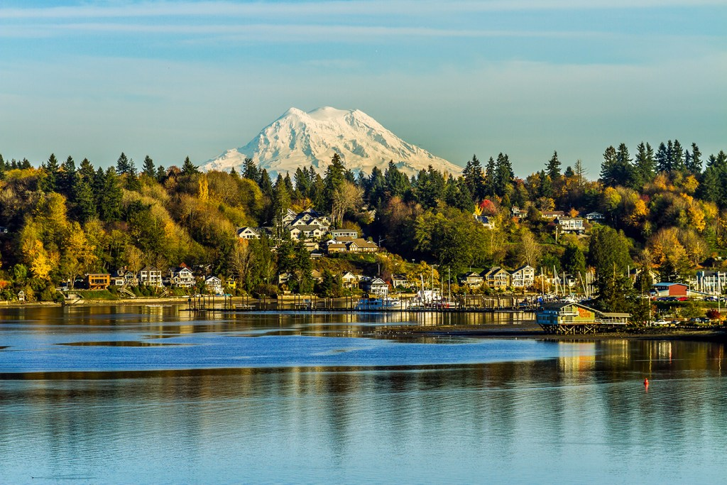 The waterfront in Olympia, Washington, with buildings by the water and a snowy mountain in the distance