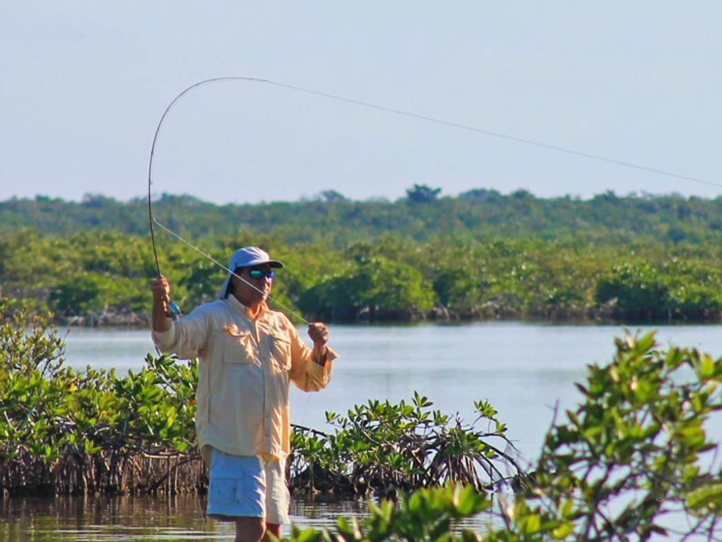 A man casts a fishing line into the marshy lagoon waters of Cozumel