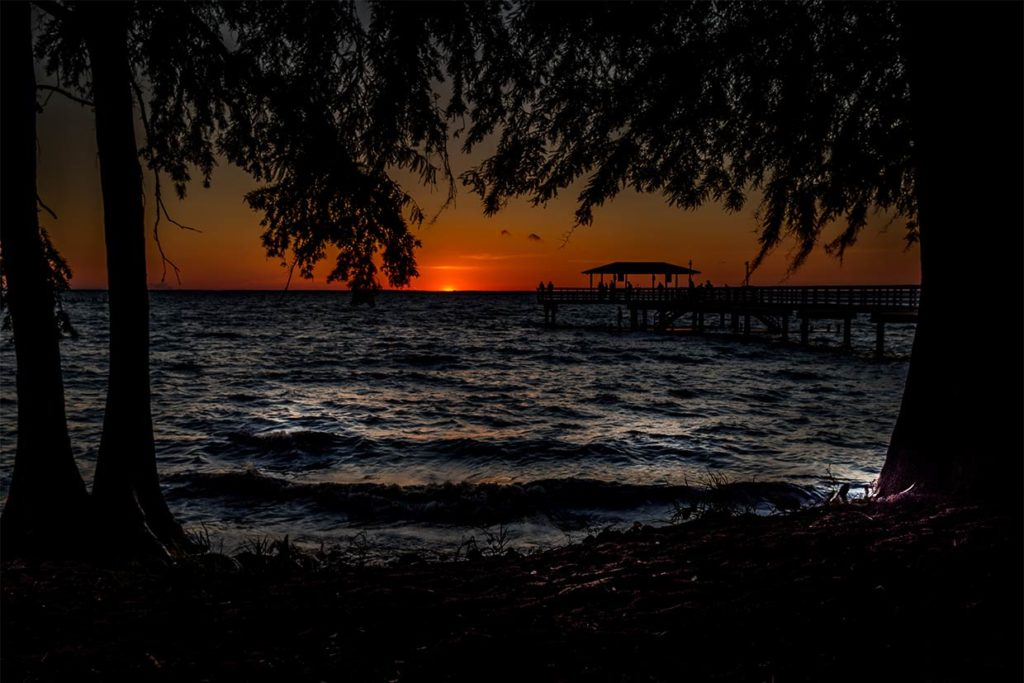 A view of Mobile Bay at sunset with a fishing pier on the right