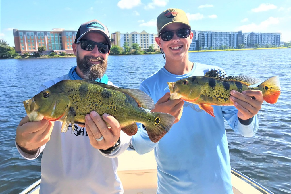Two happy anglers holding Peacock Bass caught while fishing in Miami