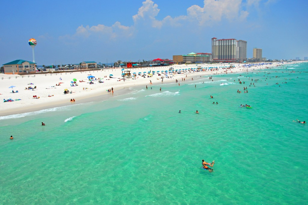 A busy summer's day on Pensacola Beach, with lots of people in the sea and on the beach