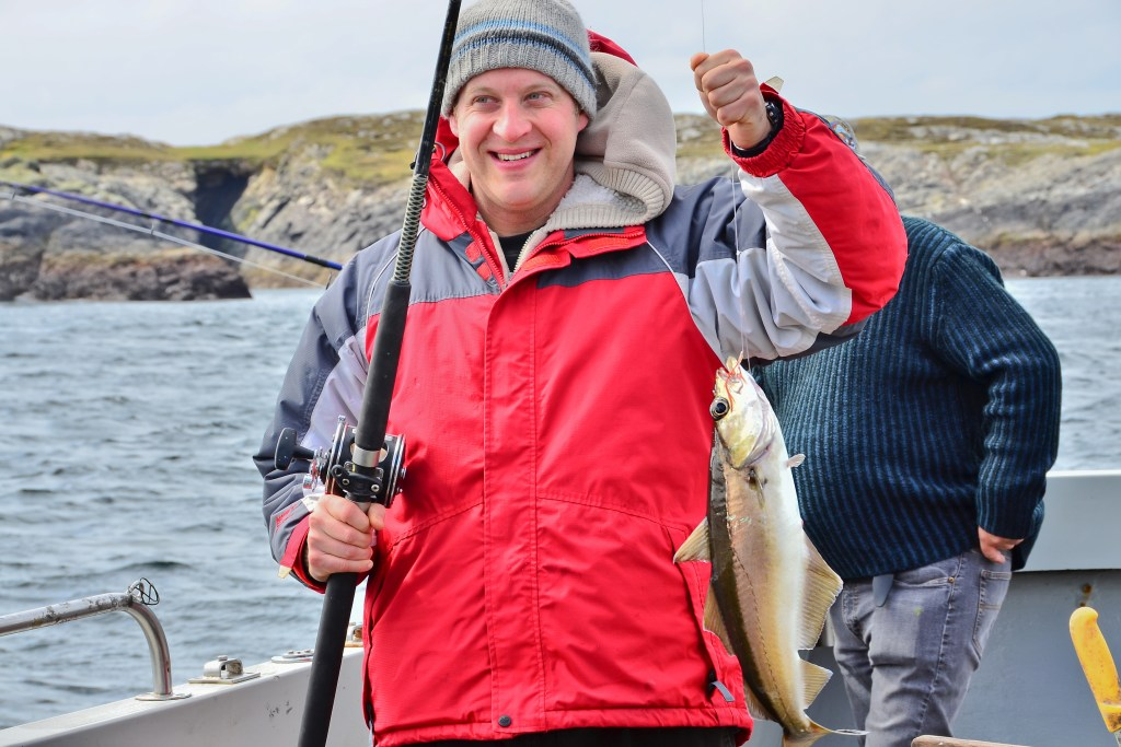 An angler in a red jacket holding a fishing rod in one hand and a Pollock in the other. He is on a boat, with water and a rocky shoreline behind him.