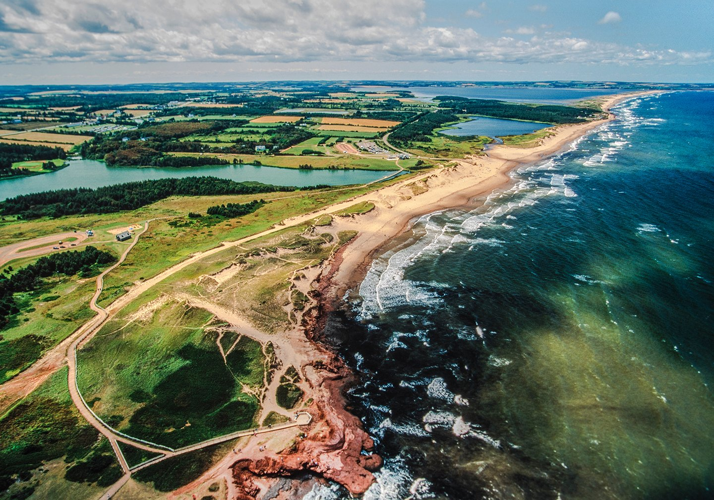 An aerial view of Prince Edward Island in Canada, with green fields on the left, yellow beach in the middle, and dark green water on the right
