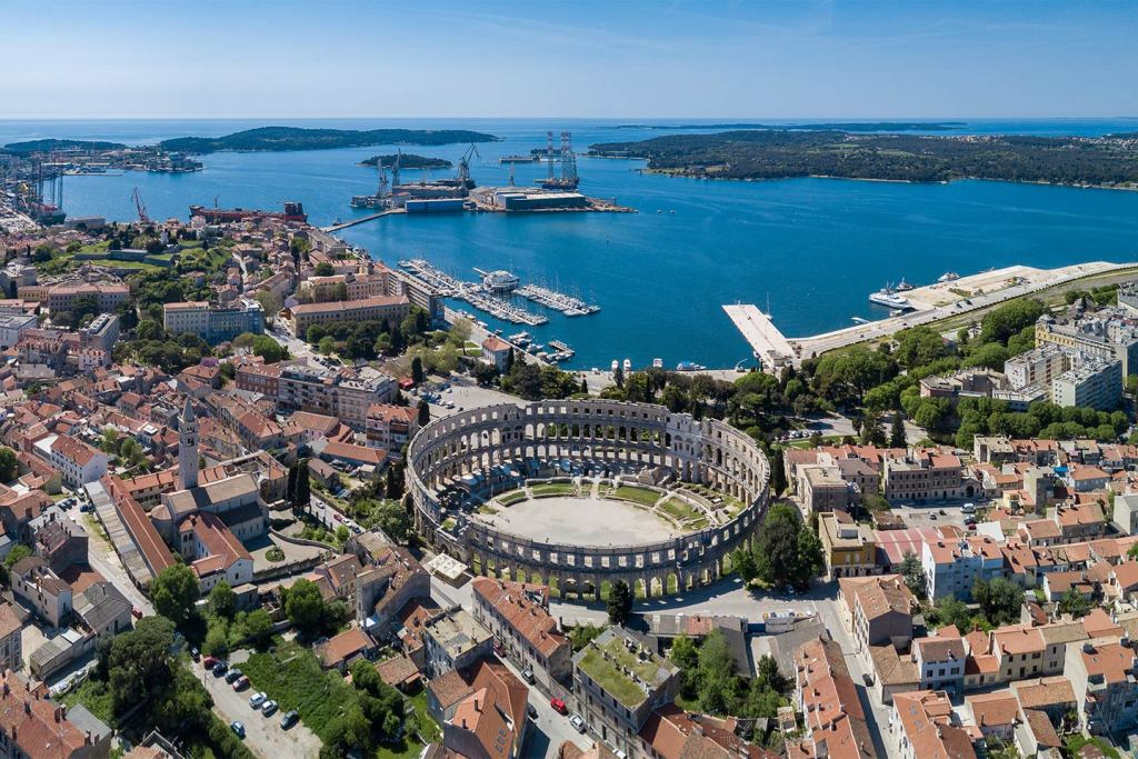 An aerial view of the town of Pula with the Roman amphitheatre in the foreground and the harbour in the background