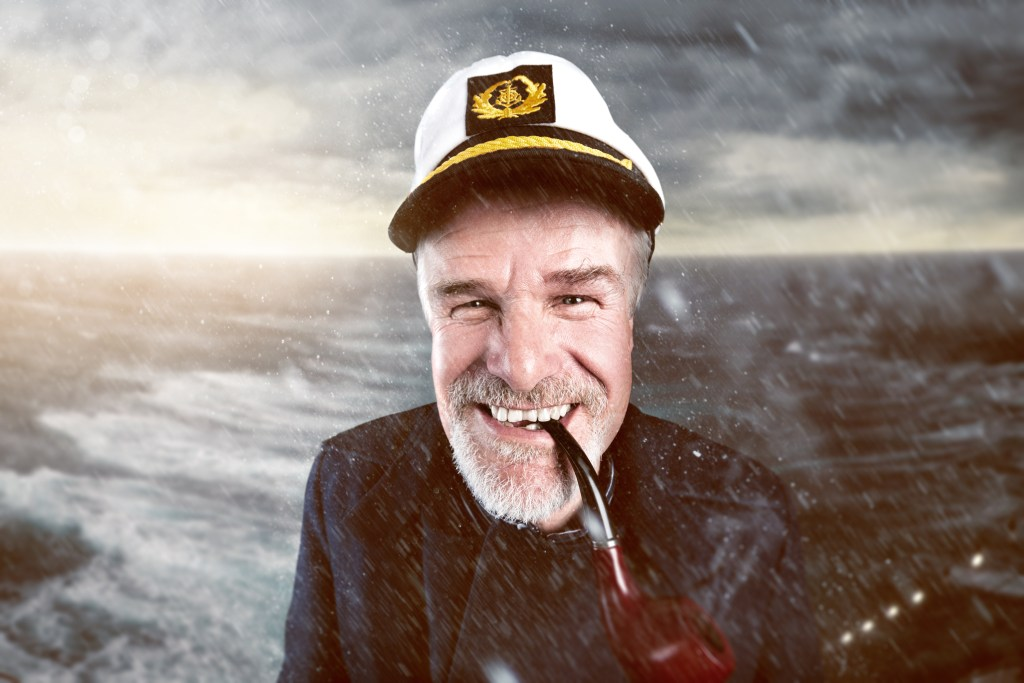 A grinning sea captain with a pipe in his mouth standing on the deck of a ship in a storm
