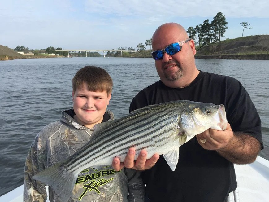 A man and a boy with a Striped Bass on a boat on Santee Cooper