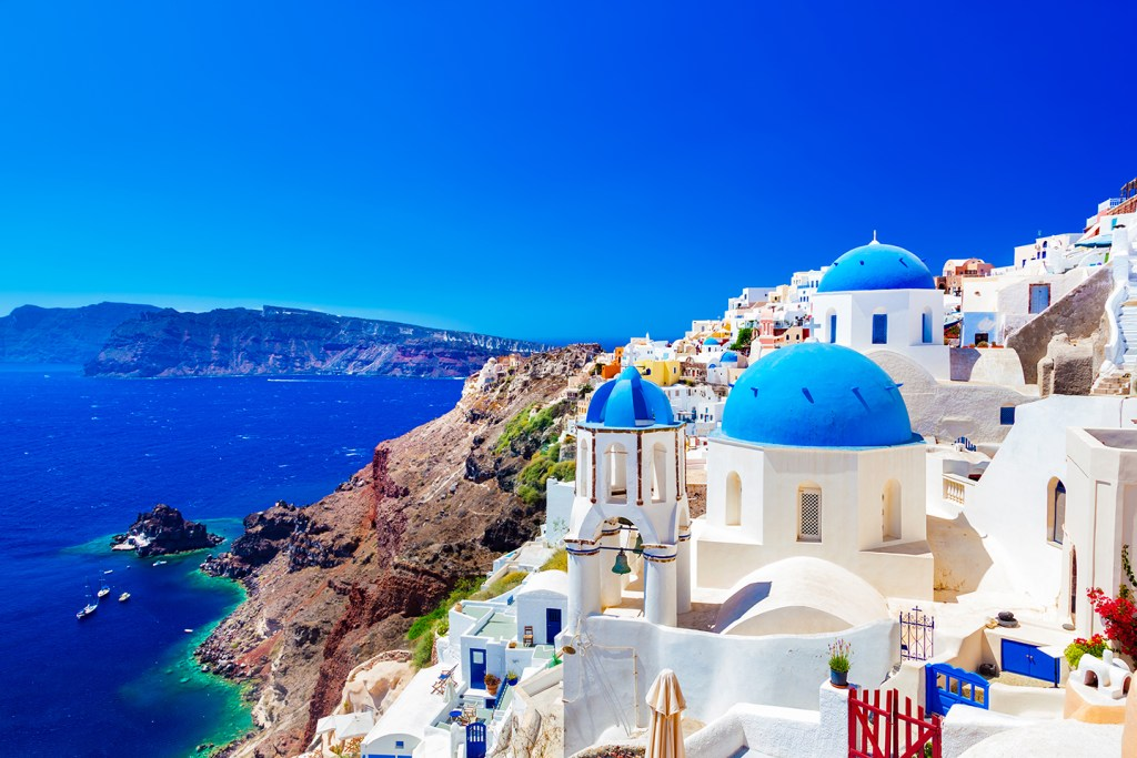 The town of Oia on Santorini, one of the most colorful fishing towns in the world, with whitewash buildings and blue domes overlooking the sea.