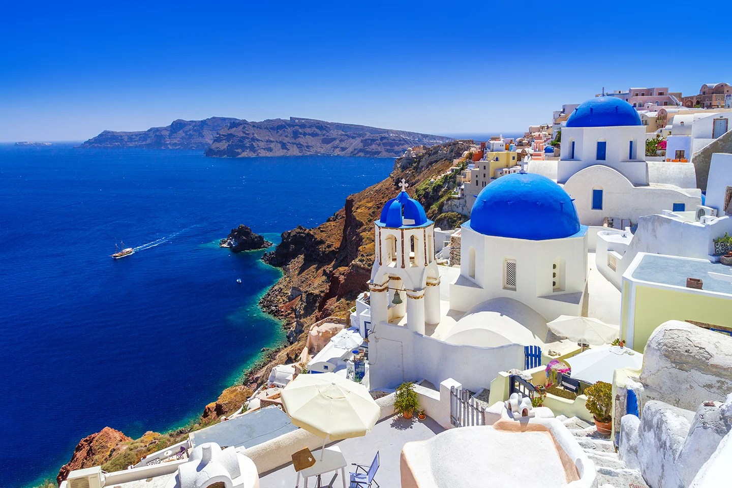 Old white buildings with blue roofs on Santorini, Greece. There is a small fishing boat in the sea on the left.