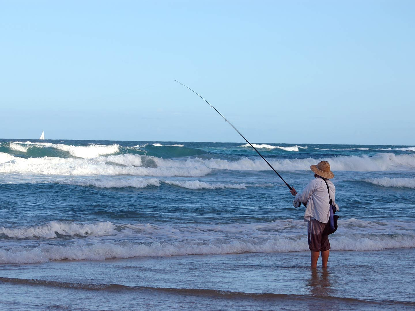 An angler fishing from a beach as the waves are coming in