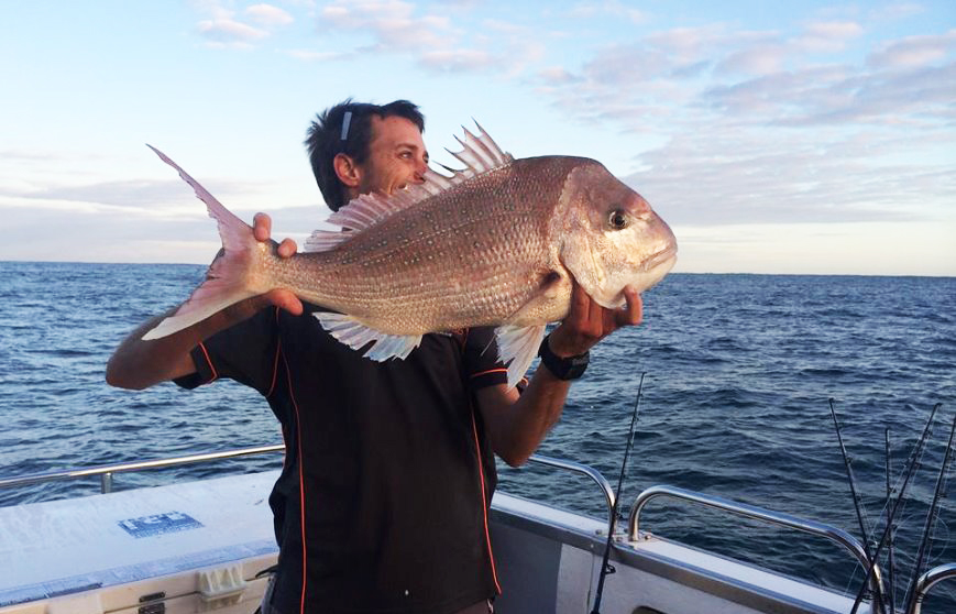 smiling angler holding a Snapper on a fishing boat