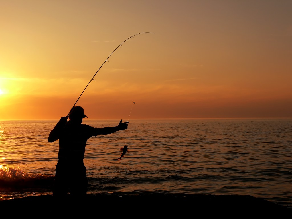 Solo angler reeling in his catch at sunset