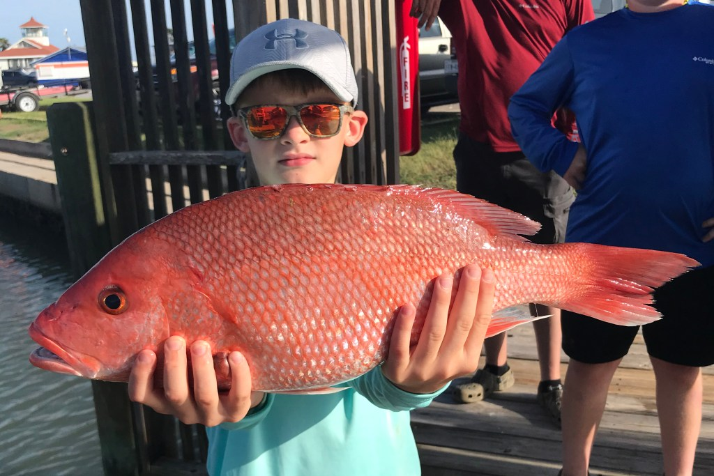 A boy holding a Red Snapper caught on a South Padre Island fishing trip