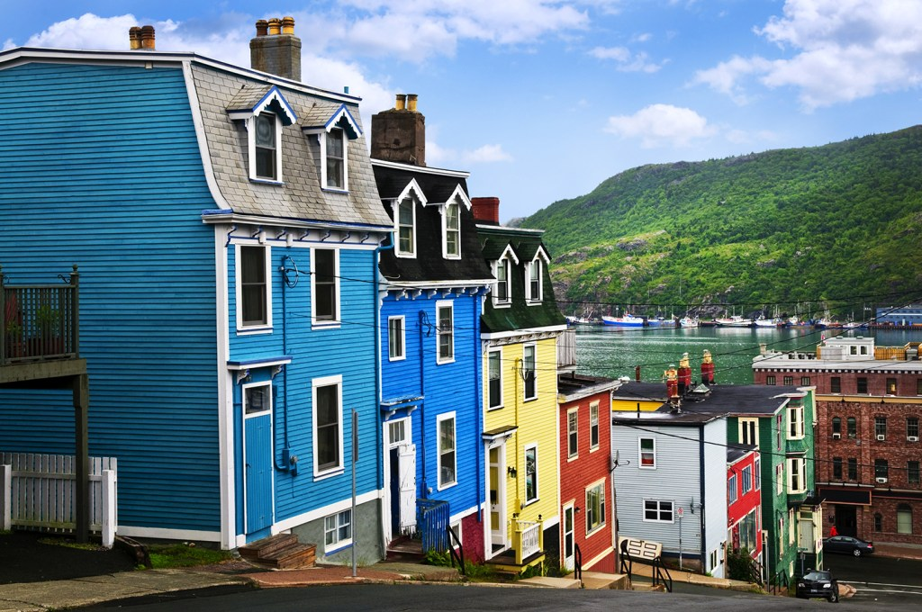 A row of traditional clapboard houses in St. John's, Newfoundland, in a variety of jolly colors. Boats are visible in the sea behind the houses, with green hills in the distance.