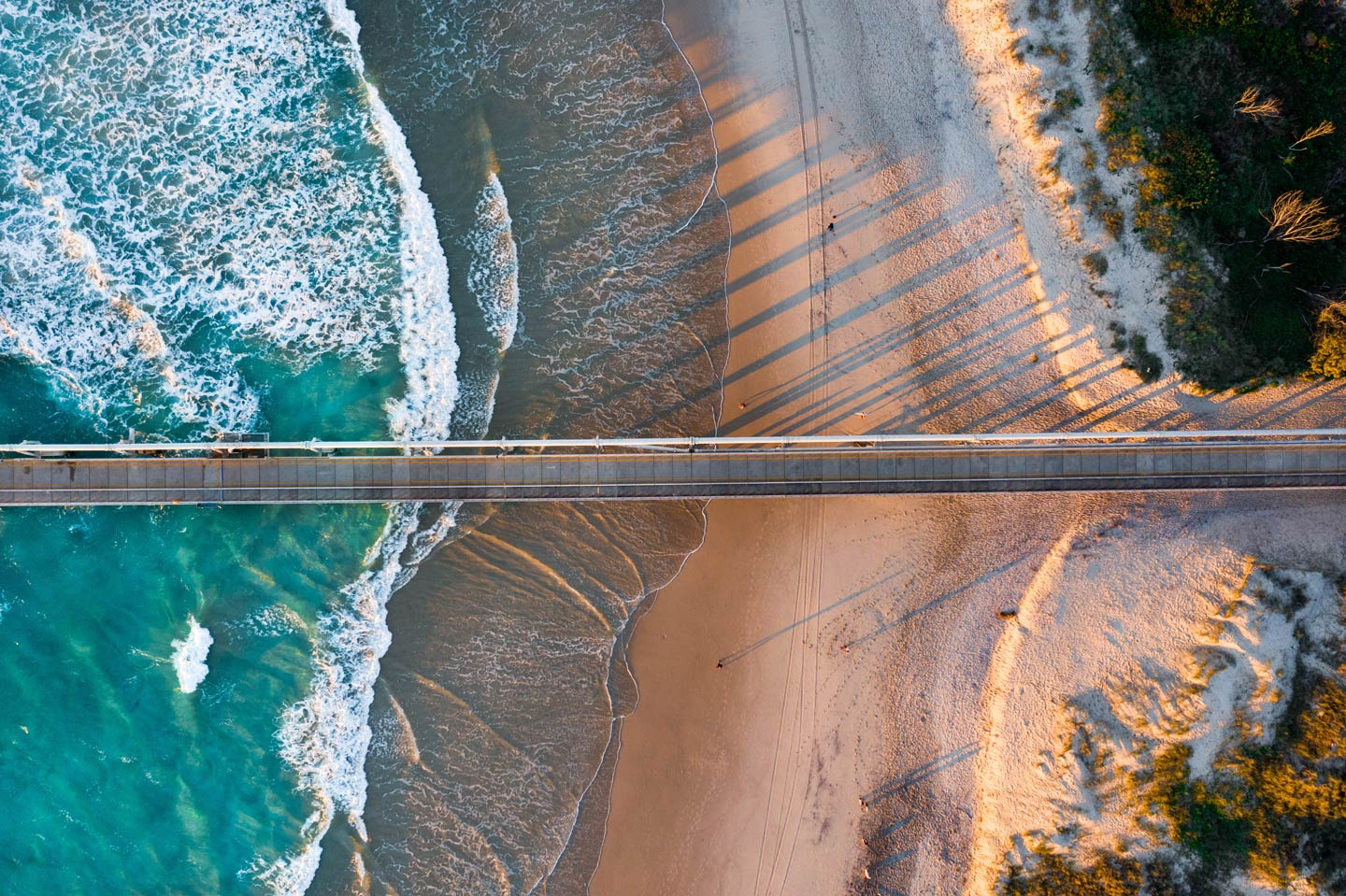 An aerial view of a sunrise over Sebastian Inlet, showing the waves crashing against the shore and the pier
