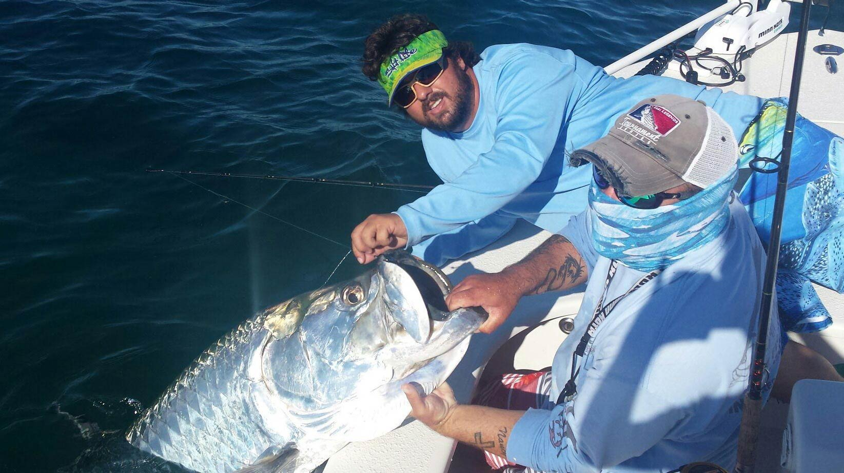 Two anglers leaning off the edge of the boat, holding a massive Tarpon