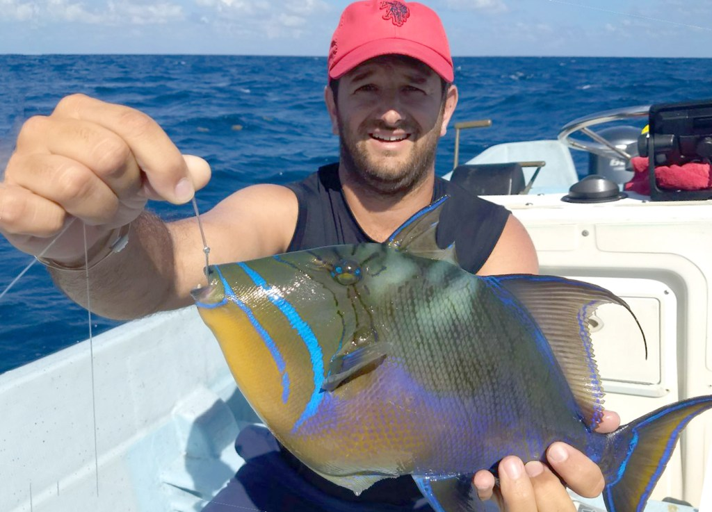a smiling angler holding a triggerfish on a fishing boat in riviera maya