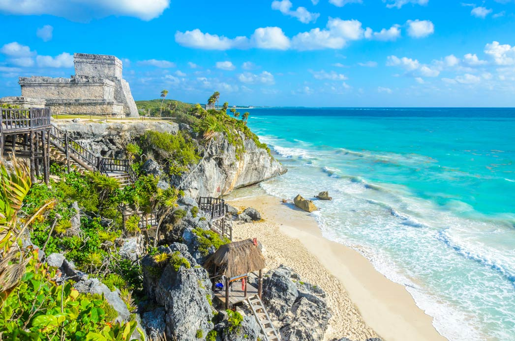 Tulum's coastline on a sunny day, showing the beach and the sea as well as Mayan ruins
