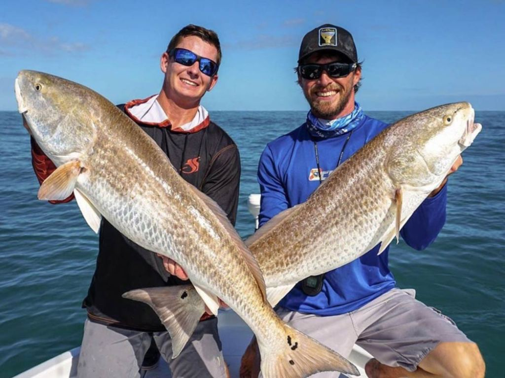 Two men posing on a boat on the Indian River, holding two big Redfish