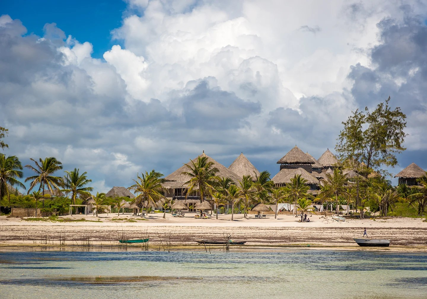 A view taken from the sea of traditional huts in Watamu, Kenya. There is shallow, clear water in the foreground and cloudy sky in the distance