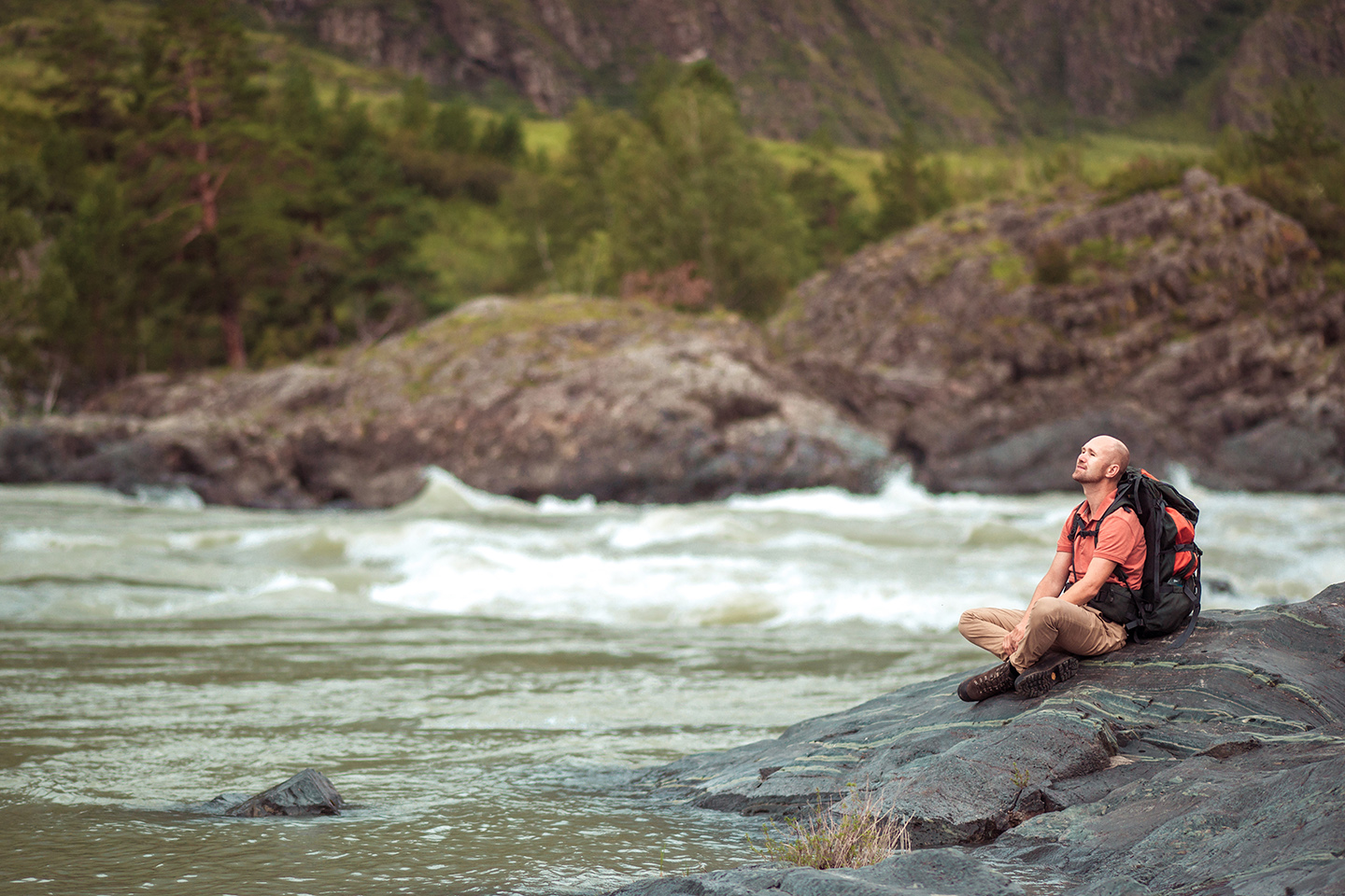 A man sitting and breathing deeply by the side of a rushing river