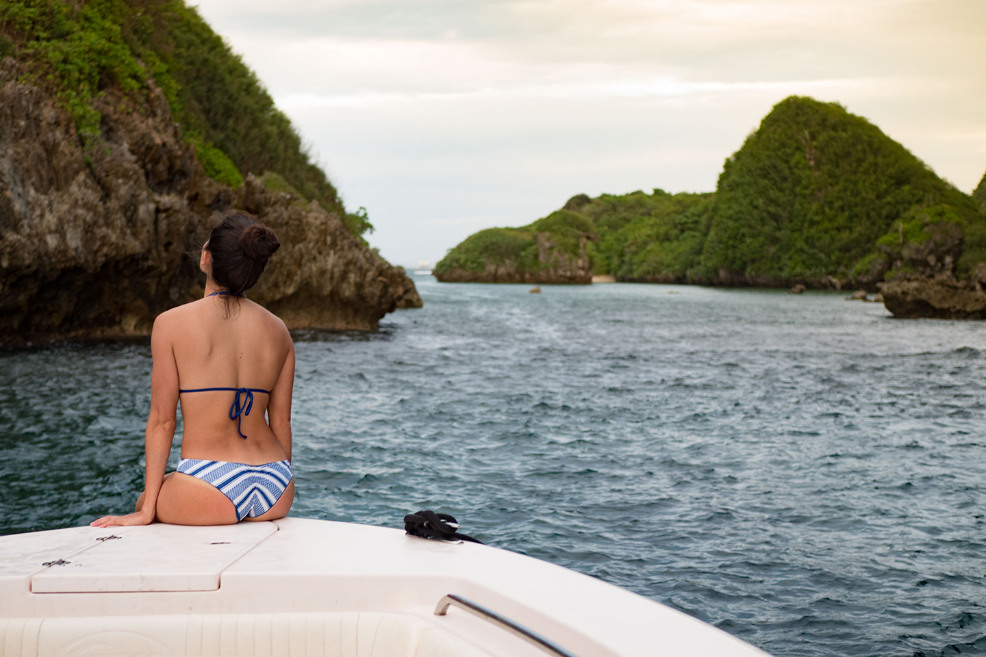 a woman in a bikini sitting at the front of a boat, with tall rocks in the distance
