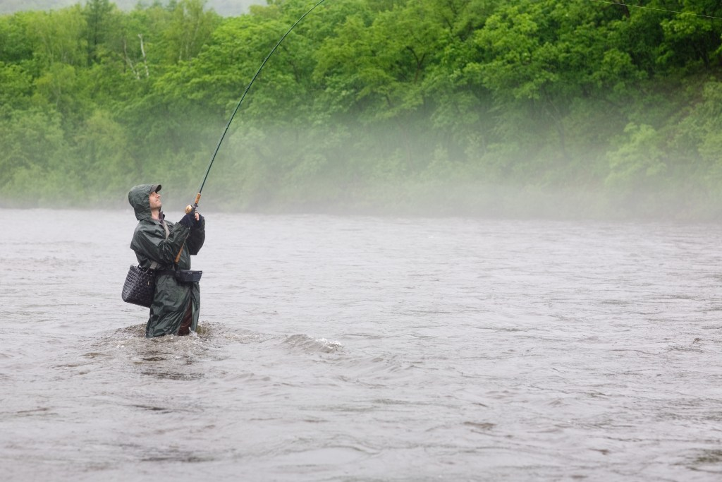 angler fishing in a river in the rain