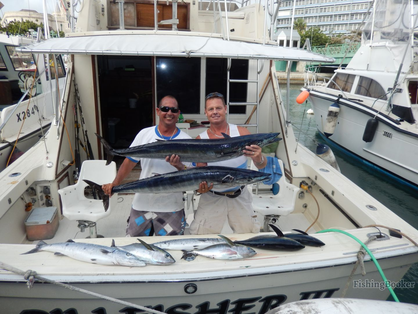 Two smiling anglers on a fishing boat, each holding a Wahoo in their hands, with several other fish in front of them