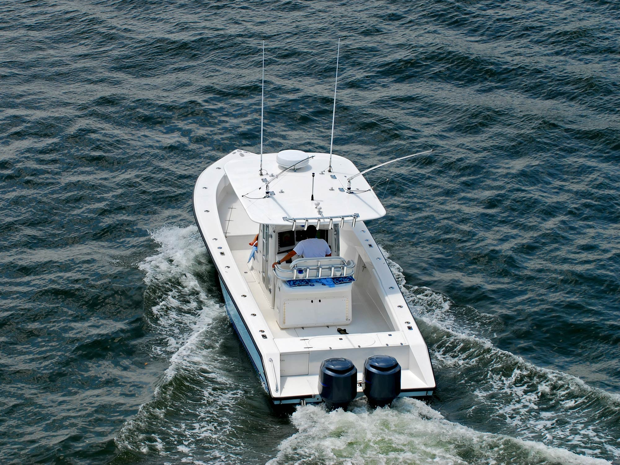 Center console fishing boat speeding away from the shore