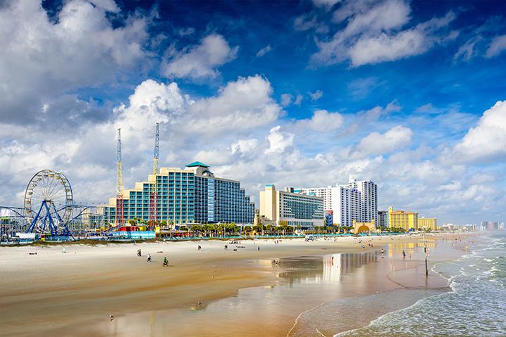 The cityscape of Daytona Beach with people sunbathing on sand